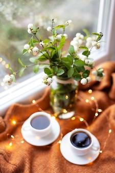 Tassen kaffee nahe fenster mit blumenstrauß