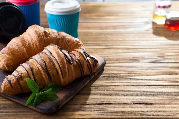 Tassen kaffee und zwei hörnchen auf der straße in croissant cafe