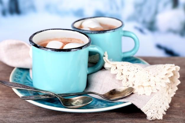 Tassen leckerer heißer kakao, auf holztisch, auf heller oberfläche