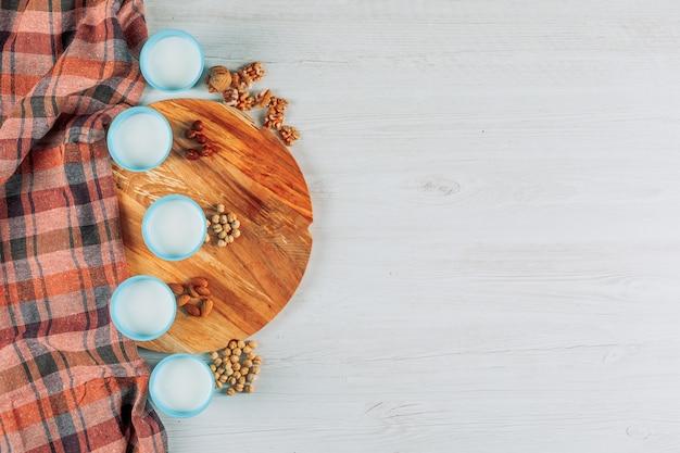Tassen milch mit haselnüssen, mandeln und mehreren nüssen hohe winkelansicht auf einem weißen hölzernen, picknicktuch und hölzernen schneidebretthintergrund