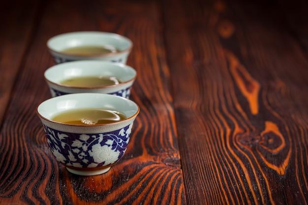 Tassen mit grünem tee auf holz