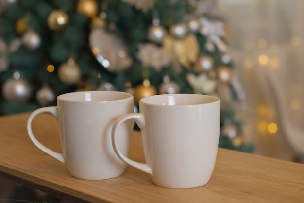 Tassen mit heißem getränk auf bokeh-hintergrund in weihnachten