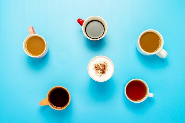 Tassen mit heißen getränken, kaffee, cappuccino, kaffee mit milch auf einer blauen fläche. konzept café, freunde treffen, frühstück