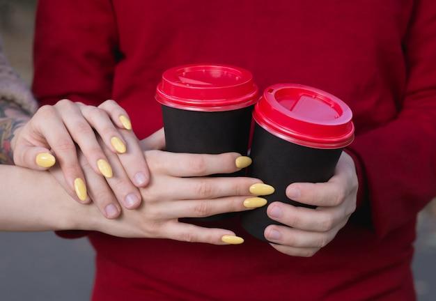 Tassen mit kaffee in den händen der jugendlichen