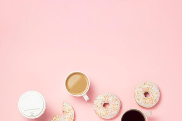 Tassen mit kaffee oder tee, frische leckere süße donuts auf einem rosa hintergrund. fast-food-konzept, bäckerei, frühstück, süßigkeiten, café. flache lage, draufsicht, kopierraum.