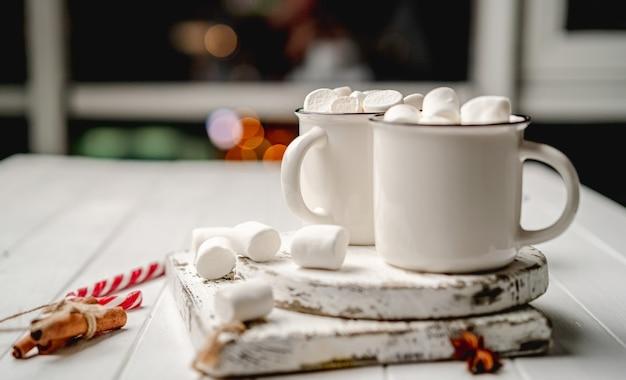 Tassen mit kakao stehen neben marshmallow