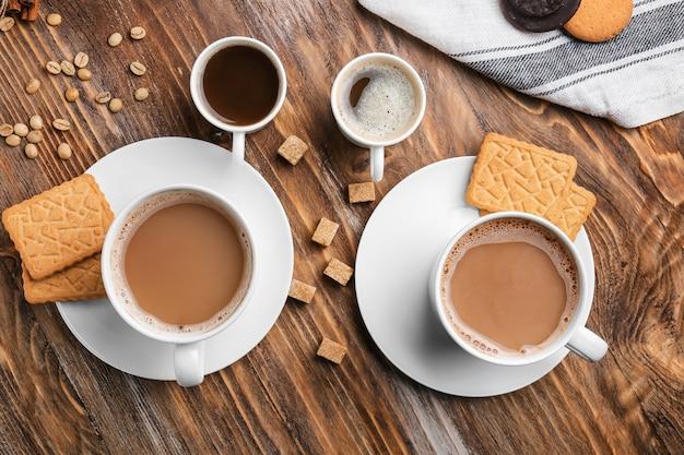 Tassen mit leckerem aromatischem kaffee und keksen auf holztisch