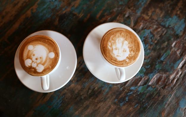 Tassen mit leckerem cappuccino stehen auf dem strukturierten holztisch mit einigen farben darauf.