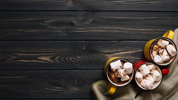 Tassen mit marshmallows in der nähe von tuch