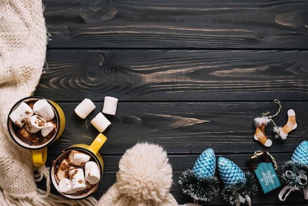 Tassen mit marshmallows in der nähe von warmer kleidung und weihnachtsspielzeug