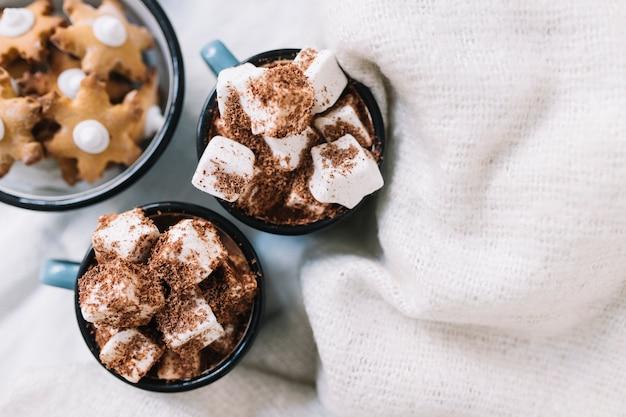 Tassen mit marshmallows und sternplätzchen