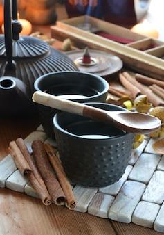 Tassen schwarzer tee begleitet von weihrauch, zimt und kerzen