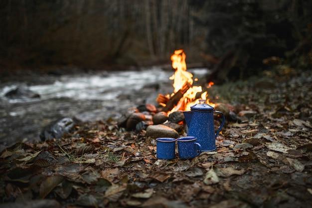 Tassen und lagerfeuer in der nähe von stream