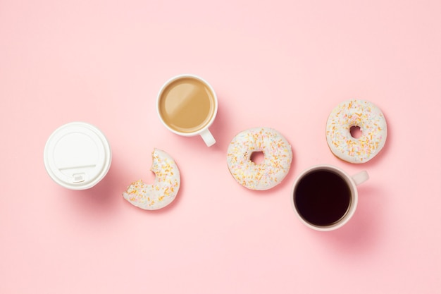 Tassen und pappbecher mit kaffee oder tee, frische leckere süße donuts auf einem rosa hintergrund. fast-food-konzept, bäckerei, frühstück, süßigkeiten, café. flache lage, draufsicht, kopierraum.