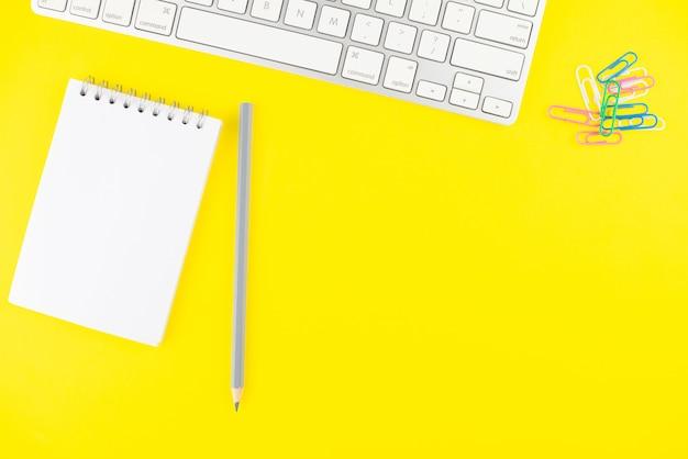 Tastatur, bleistift, notizblockplaner und bunte clips auf gelbem hintergrund.
