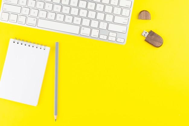 Tastatur, bleistift, usb-blitz und notizblockplaner auf gelbem hintergrund.