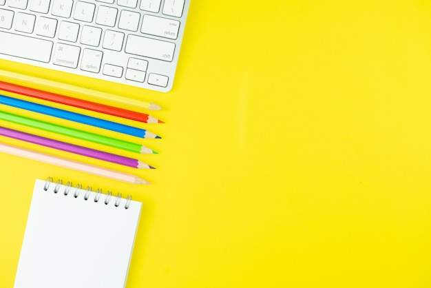 Tastatur, bunte pensils und notizblockplaner auf gelbem hintergrund