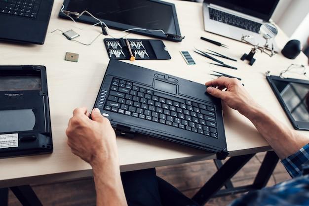 Tastatur des zerlegten laptops in männlichen händen