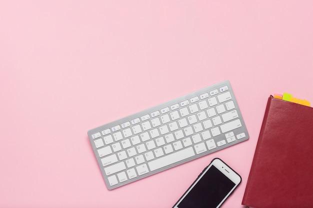 Tastatur, handy und tagesprotokoll auf einem rosa hintergrund. geschäftskonzept. flache lage, draufsicht.