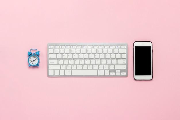 Tastatur, handy und wecker auf einem rosa hintergrund. geschäftskonzept. flache lage, draufsicht.
