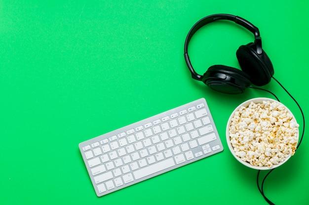 Tastatur, kopfhörer und eine schüssel popcorn auf einem grünen hintergrund. das konzept, filme, shows, sport auf der ps und online-spiele anzusehen. flache lage, draufsicht.