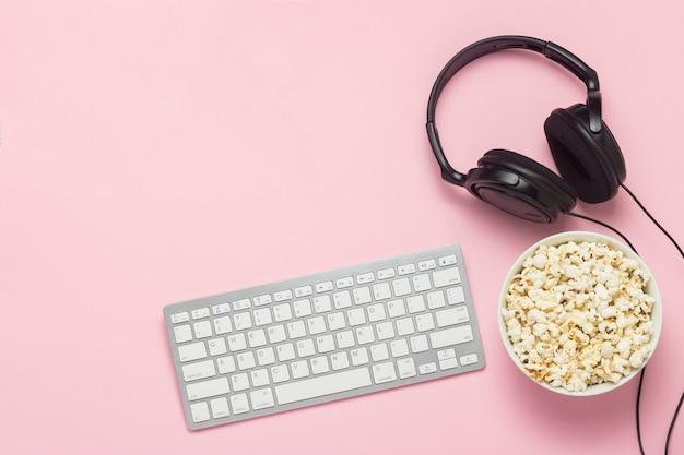 Tastatur, kopfhörer und eine schüssel popcorn auf einem rosa hintergrund. das konzept, filme, shows, sport auf der ps und online-spiele anzusehen. flache lage, draufsicht.