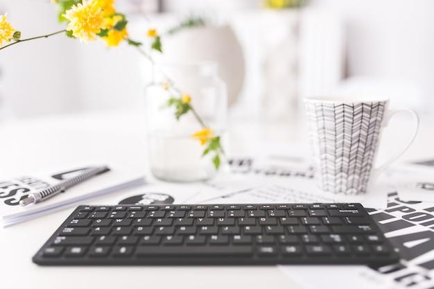 Tastatur mit gelben blumen und eine tasse