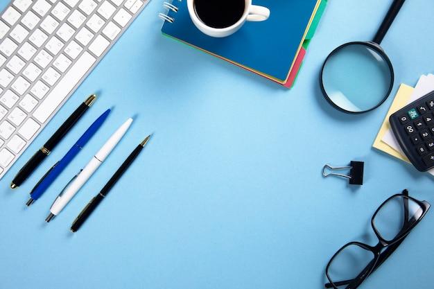 Tastatur mit notizblock und kaffee mit stationärem tisch