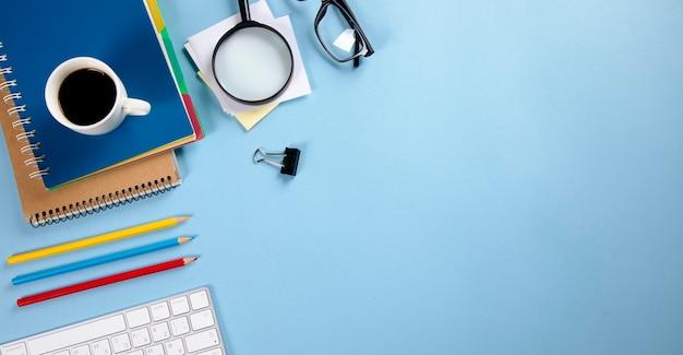 Tastatur mit notizbuch und stiften mit kaffee auf arbeitstisch