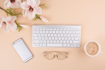 Tastatur mit Smartphone und Blumen auf dem Tisch
