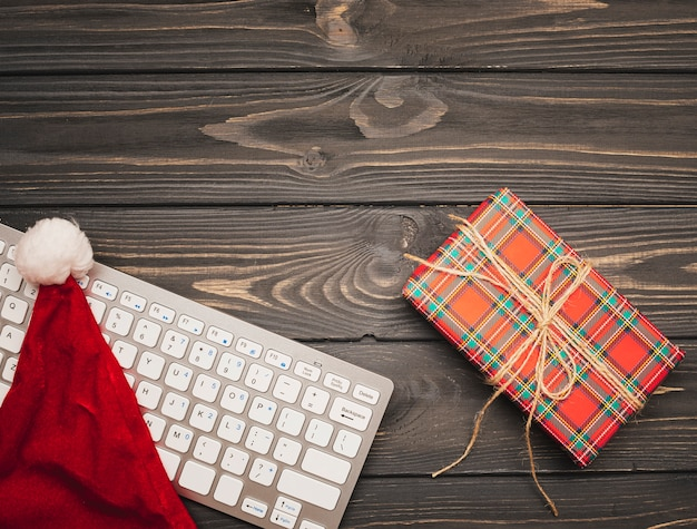 Tastatur mit weihnachtshut auf hölzernem hintergrund