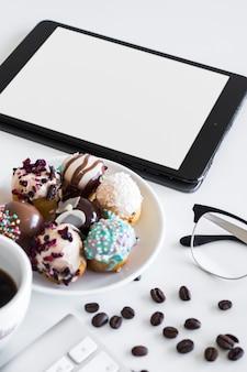 Tastatur nahe schale, tablette, brillen und keksen auf platte