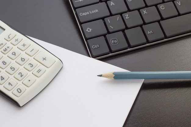Tastatur, notizbuch und taschenrechner auf dem tisch, draufsicht