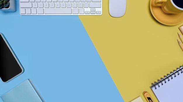 Tastatur, smartphone und kaffeetasse auf blauem und gelbem hintergrund mit zwei tönen.