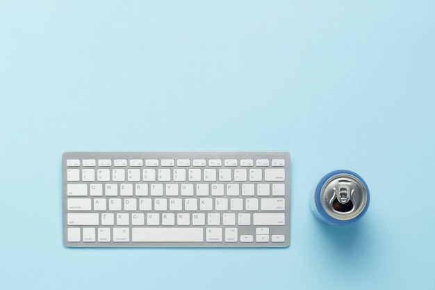 Tastatur und blechdose mit einem getränk, energiegetränk auf einem blauen hintergrund. geschäftskonzept, arbeiten am computer, online-spielen von ps, filmen und tv-shows. flache lage, draufsicht.