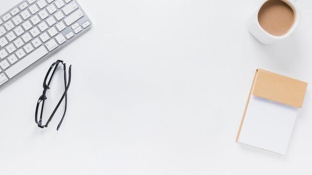 Tastatur und brille in der nähe von notizblock und kaffeetasse