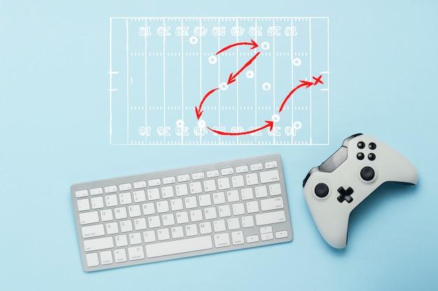 Tastatur und gamepad auf blauem grund. gekritzel zeichnen mit taktik des spiels. american football. das konzept von computerspielen, unterhaltung, spielen, freizeit. flache lage, draufsicht.