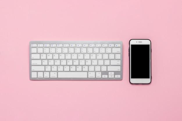 Tastatur und handy auf einem rosa hintergrund. geschäftskonzept. flache lage, draufsicht.
