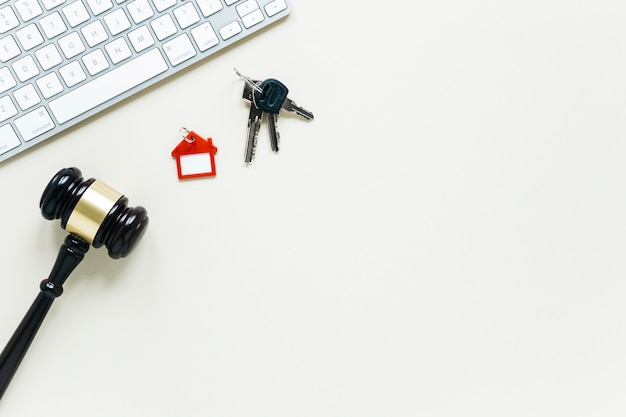 Tastatur und keychain mit hölzernem hammer auf weißem hintergrund