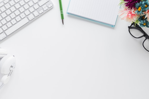 Tastatur und kopfhörer in der nähe von briefpapier und brille