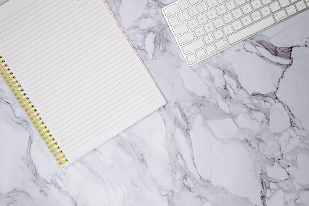 Tastatur und notebook auf marmoroberfläche