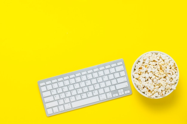 Tastatur und schüssel mit popcorn auf gelbem grund. das konzept, filme, fernsehsendungen, shows und sport online zu schauen. flache lage, draufsicht.