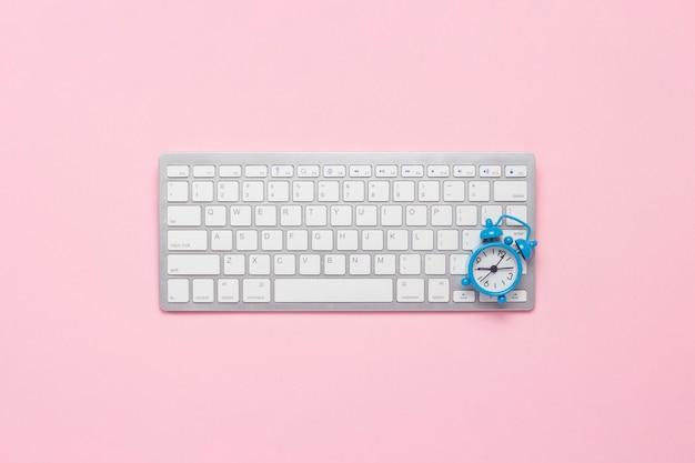 Tastatur und wecker auf einem rosa hintergrund. flache lage, draufsicht.
