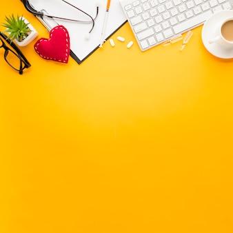Tastatur; zwischenablage; genähte herzform; medizin; injektion; brillen und stethoskop; tasse tee angeordnet auf gelbem oberflächenboden