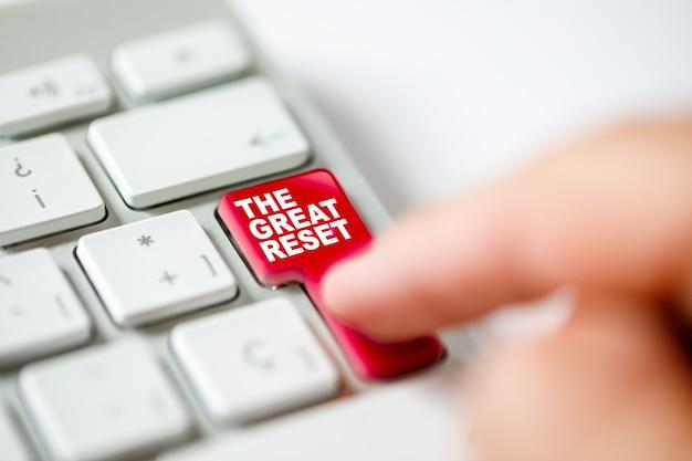 Tastaturtaste mit einem finger gedrückt, der das great reset-konzept darstellt