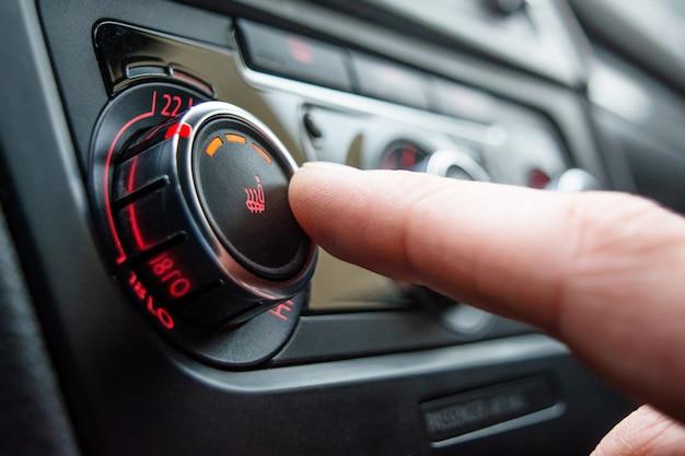 Taste zum heizen der autositze in nahaufnahme. die männliche hand drückt den knopf zum heizen der autositze.