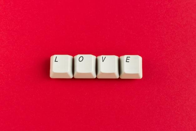 Tasten mit dem liebeswort geschrieben unter verwendung der weißen knöpfe auf roten hintergrund.