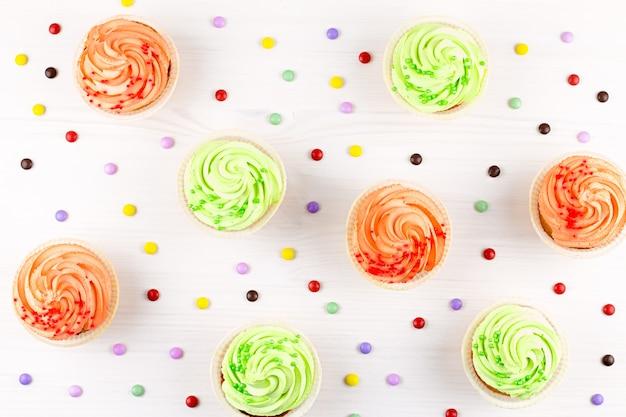 Tasty bunte cupcakes nahaufnahme auf bokeh hintergrund mit kopienraum. geburtstagsfeier süßigkeiten