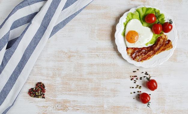 Tasty fried egg in form eines herzens, das auf einer weißen platte mit speck-tomaten-salat serviert wird, verlässt pfeffer hölzernen hintergrund valentine day morning