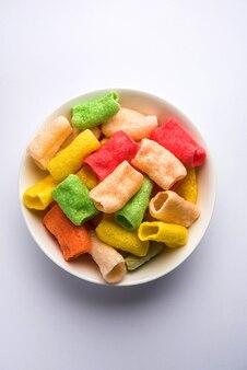 Tasty papad pipe fryum ist ein mehrfarbiges snack-pellets auf kartoffelbasis in röhrenform, serviert in einer schüssel